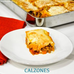 Deep-Dish Pan Calzones are a stuffed pizza recipe using a large thin pizza dough that literally wraps your favorite pizza toppings in dough in a 13x9 pan.
