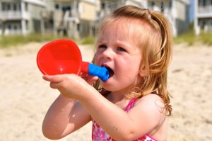 little girl chewing on sand toy
