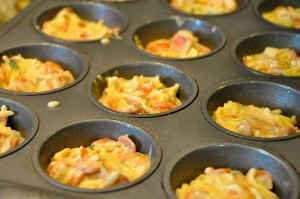 muffin tins filled with pizza batter