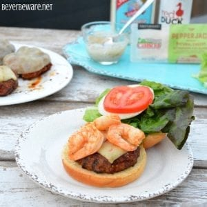 The Cajunpork burgers topped with shrimp and then drenched in a Cajun aioli combine ground pork, chorizo, with a Cajun seasoned horseradish mayonnaise for a perfect surf and turf burger recipe.