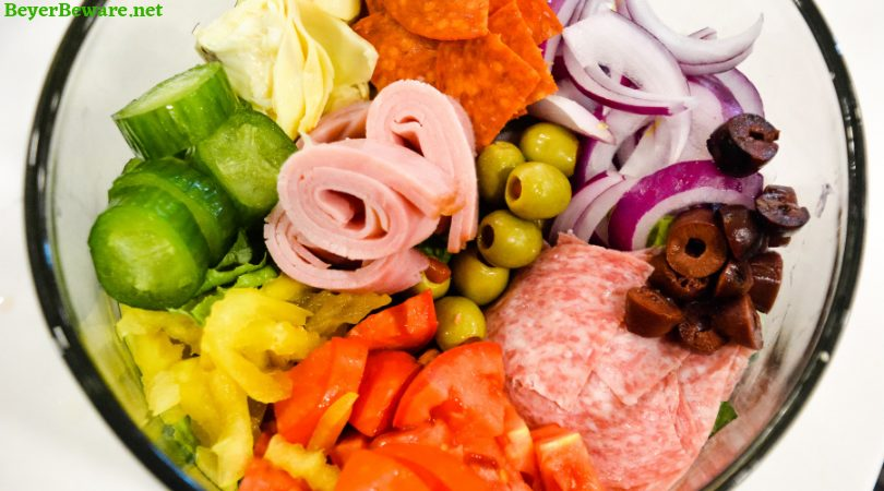 Italian antipasto salad is a hearty dinner salad with a romaine lettuce base and filled up with salami, pepperoni, tomatoes, cucumbers, onions, olives, banana peppers, artichoke hearts and cheese dressed with a homemade Italian dressing.