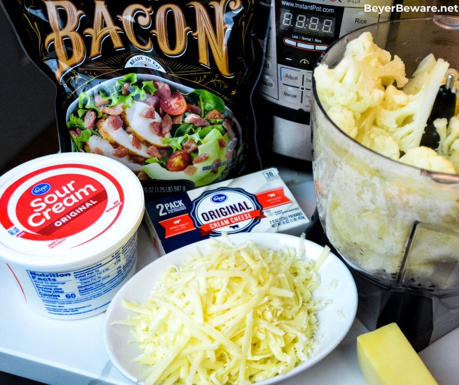 Keto mashed cauliflower casserole is loaded with white cheddar cheese and bacon while made smooth as mashed potatoes with sour cream and cream cheese as it bakes to perfection.