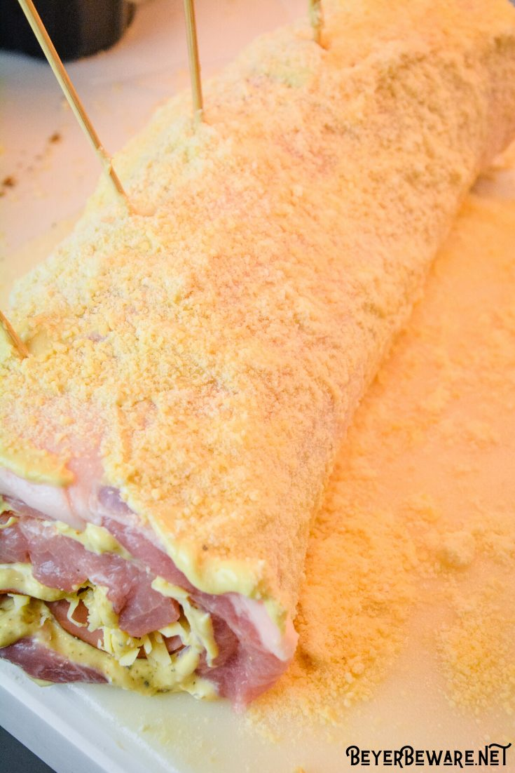 Cordon bleu pork loin recipe is stuffed full of ham and swiss cheese rolled up in a creamy mustard sauce and encrusted in a parmesan crust.