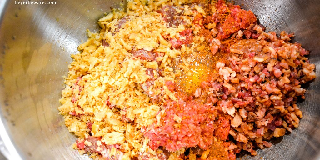 Making meatballs with the ground beef, bacon pieces, fried onions, eggs, and seasonings.
