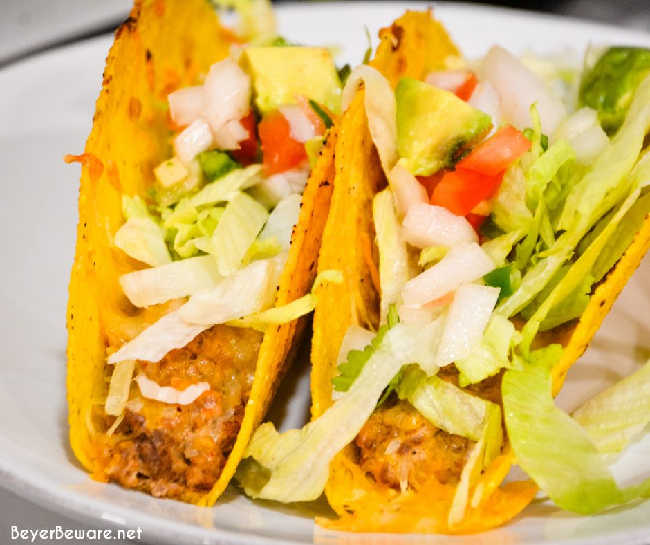Two ground beef baked tacos with toppings
