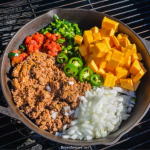 Smoked queso is your favorite queso dip made with Velveeta, Rotel, onions, taco meat, and peppers made in a cast-iron skillet on your smoker or grill.