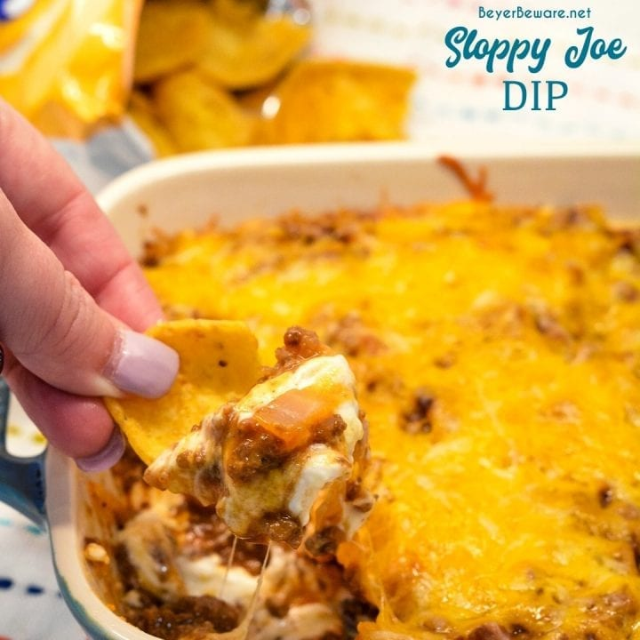 Sloppy Joe Dip has a cream cheese base and topped with an easy sloppy joe ground beef mixture and topped off with shredded cheese and onions, baked to a gooey, meaty goodness and then scooped up with corn chips.