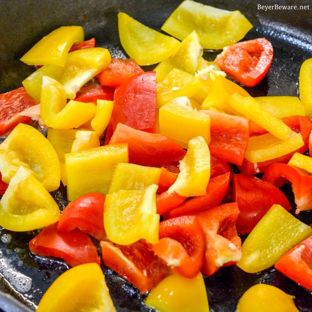 bell peppers sautéing in a cast iron skillet