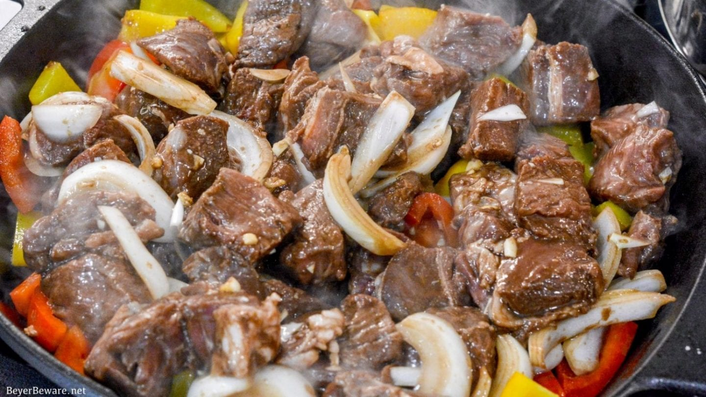 Garlic pepper steak bites recipe is an easy cast iron steak skillet meal made with an easy marinated sirloin steak recipe, garlic, onions, and bell peppers served over mashed potatoes or rice.