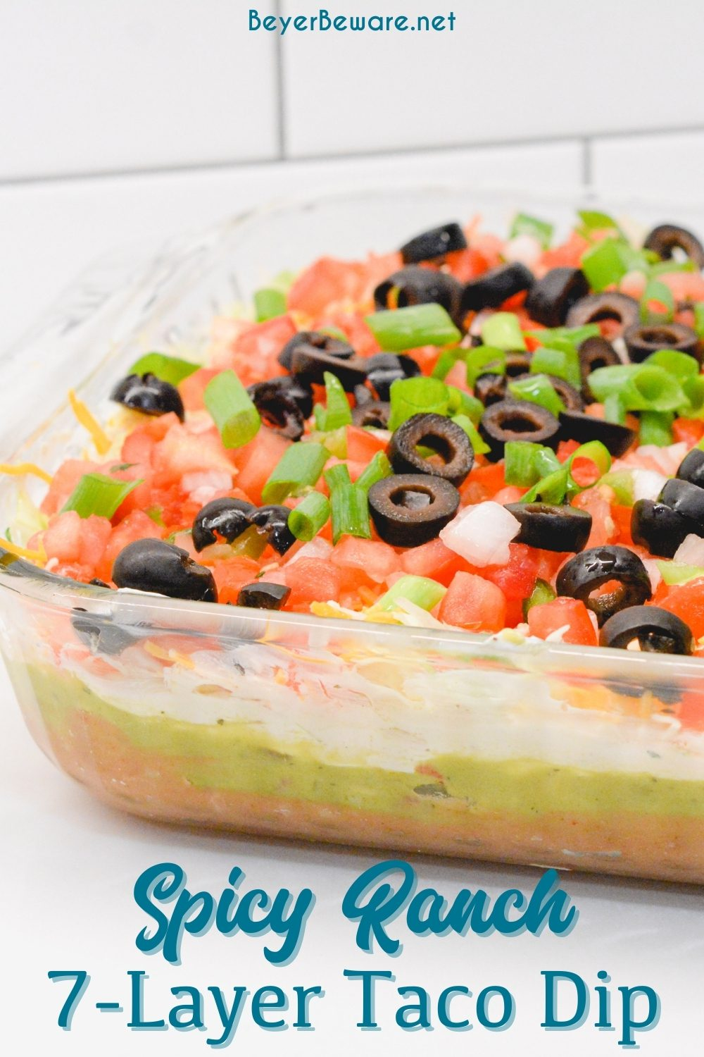 Spicy ranch 7-layer taco dip is Layers of taco-seasoned refried beans, guacamole, sour cream with ranch, lettuce, cheese, pico de gallo, olive, and cheese!