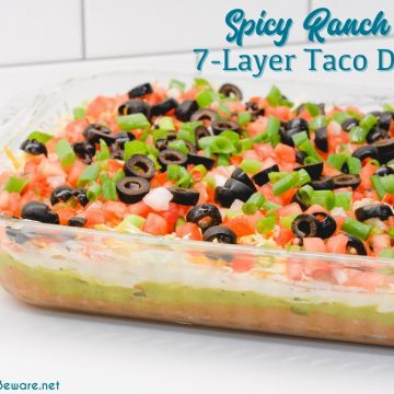 Spicy ranch 7-layer taco dip is Layers of taco-seasoned refried beans, guacamole, sour cream with ranch, lettuce, cheese, pico de gallo, olive, and cheese.