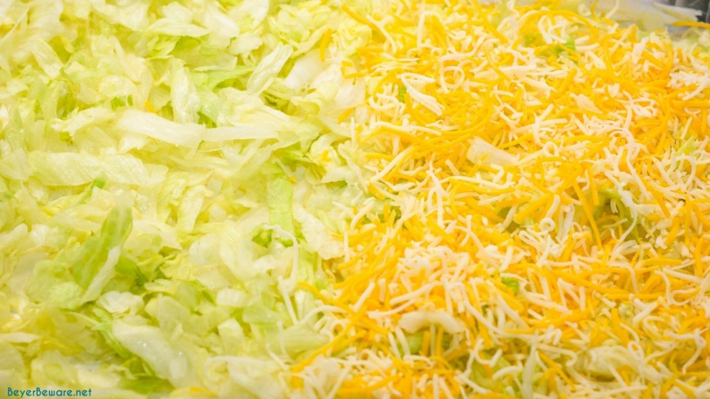 Lettuce and shredded cheese layer of the 7 layer dip.